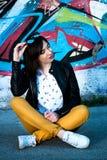 Jeune fille s'asseyant sur le plancher dans la belle journée de printemps devant le graffiti sur le mur à l'arrière-plan Photos stock