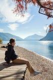 Jeune fille s'asseyant sur le rivage de lac en parc d'automne Lugano Photo stock