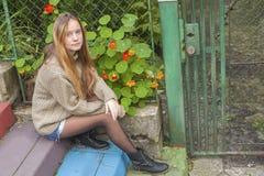 Jeune fille s'asseyant sur les étapes près de la maison de campagne Image libre de droits