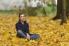 Jeune fille s'asseyant sur les feuilles tombées en parc d'automne nature Images libres de droits