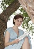 Jeune fille s'asseyant sur un arbre et affichant un livre Photos stock