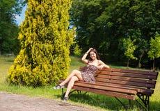 Jeune fille s'asseyant sur un banc de parc Images libres de droits