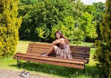 Jeune fille s'asseyant sur un banc de parc Images stock