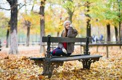 Jeune fille s'asseyant sur un banc en parc Photo stock