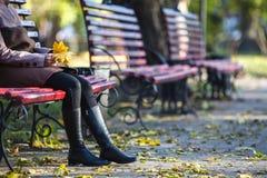 Jeune fille s'asseyant sur un banc en parc un jour d'automne Image stock