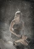 Jeune fille s'asseyant sur un plancher dans la maison de taudis Photographie stock libre de droits