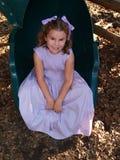 Jeune fille s'asseyant sur une glissière Image libre de droits