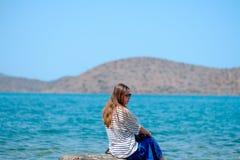 Jeune fille s'asseyant sur une jetée regardant la mer et les montagnes Photo libre de droits