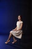 Jeune fille s'asseyant sur une présidence Photographie stock libre de droits