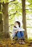 Jeune fille s'asseyant tranquillement en bois Photos libres de droits
