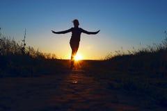 Jeune fille sautant par-dessus le fond de coucher du soleil Silhouette intégrale d'une fille heureuse courant dehors images libres de droits