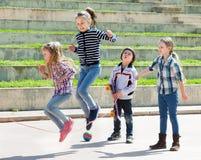 Jeune fille sautant tandis que jeu de corde de saut Photographie stock libre de droits