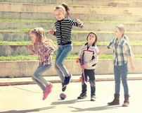 Jeune fille sautant tandis que jeu de corde de saut Photographie stock