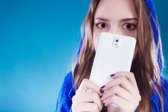 Jeune fille se cachant derrière le téléphone images libres de droits