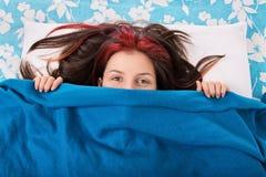 Jeune fille se cachant derrière une couverture sur son lit Photographie stock libre de droits