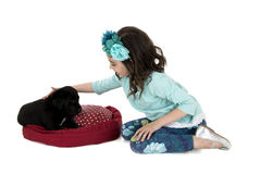 Jeune fille se mettant à genoux en bas de choyer son chiot noir de laboratoire photographie stock