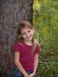 Jeune fille se penchant contre l'arbre Image libre de droits