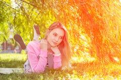 Jeune fille se reposant en parc d'été photographie stock libre de droits