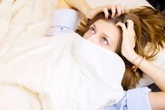 Jeune fille se situant dans son lit, visage couvert par la couverture de yeux grands ouverts avec surprise Photographie stock