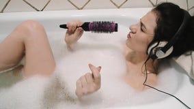 Jeune fille se situant dans un bain de mousse écoutant la musique dans des écouteurs et chantant dans une brosse à cheveux banque de vidéos
