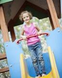 Jeune fille se tenant au sommet de la glissière dans le terrain de jeu Image libre de droits