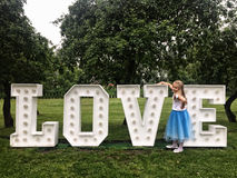 Jeune fille se tenant aux lettres au néon d'amour en parc Photographie stock