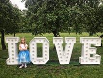 Jeune fille se tenant aux lettres au néon d'amour en parc Photos stock