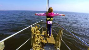 Jeune fille se tenant sur l'arc du yacht, des bras étendus et de penser à l'avenir clips vidéos