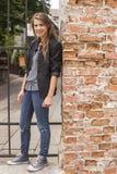 Jeune fille se tenant sur une rue près du mur de briques Été Photographie stock libre de droits