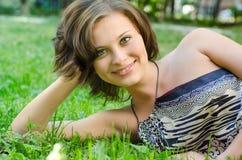 Jeune fille se trouvant sur l'herbe Images stock
