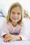 Jeune fille se trouvant sur son bâti dans des ses pyjamas Photos stock