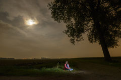 Jeune fille seul s'asseyant dans l'obscurité Images libres de droits