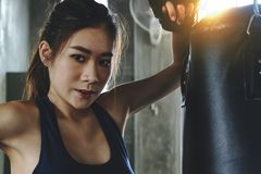 Jeune fille sexy asiatique de combattant poinçonnant activement au gymnase photo libre de droits