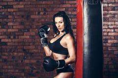 Jeune fille sexy avec des gants de boxe, sac de sable photos stock