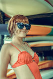 Jeune fille dans le maillot de bain rouge - surfer avec le panneau de ressac posant sur la plage de DUA de Nusa, île tropica Photo stock