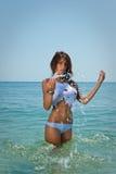 Jeune fille sexy de brune dans le bikini blanc et le T-shirt humide jouant dans l'eau Photos libres de droits