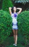 Jeune fille sexy entre deux grands buissons dans une robe courte Images libres de droits