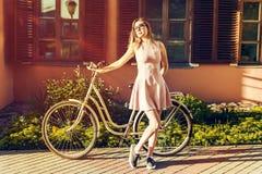 Jeune fille sexy sur une bicyclette en portrait de pose intégral dans la robe rose elle est satisfaite du soleil image libre de droits