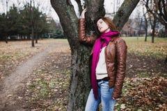 Jeune fille songeuse de brune tenant l'arbre proche Photographie stock