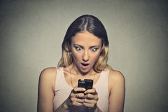 Jeune fille soucieuse regardant le téléphone voyant la mauvaise nouvelle Photographie stock libre de droits