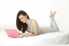 Jeune fille souriant à son ordinateur Images stock