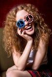 Jeune fille souriant avec les lunettes de soleil de port de cheveux bouclés avec A Photo stock