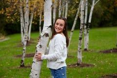 Jeune fille souriant dans un forrest des arbres de bouleau photographie stock libre de droits