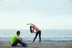 Jeune fille sportive avec un beau chiffre réchauffant avant de courir son ami la regardant Image libre de droits