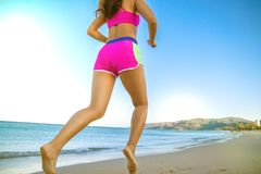 Jeune fille sportive courant sur la plage photographie stock libre de droits