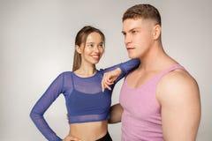Jeune fille sportive dans le dessus bleu penché sur l'épaule de son associé de forme physique dans le T-shirt rose images libres de droits
