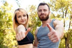 Jeune fille sportive et homme barbu sur la formation regardant le camer Image libre de droits
