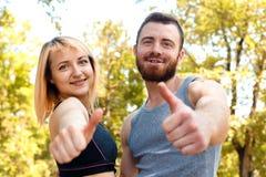 Jeune fille sportive et homme barbu sur la formation regardant le camer Image stock