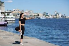 Jeune fille sportive s'étirant à la rue, près de la rivière L'espace pour le texte photo libre de droits