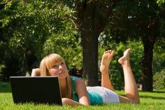 Jeune fille sur l'herbe avec le cahier Image stock